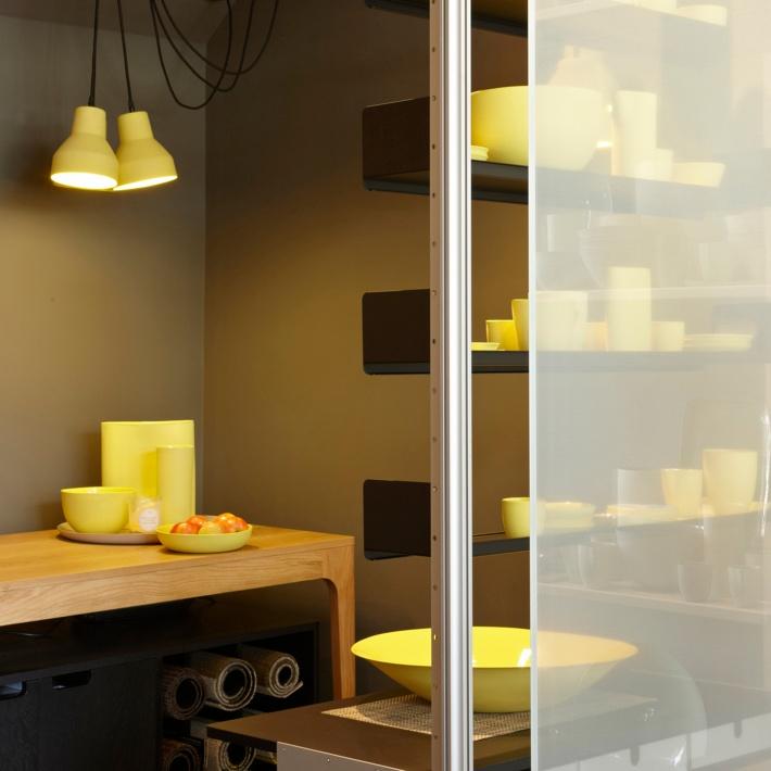 Yellow pots displayed on black shelves. Waspish
