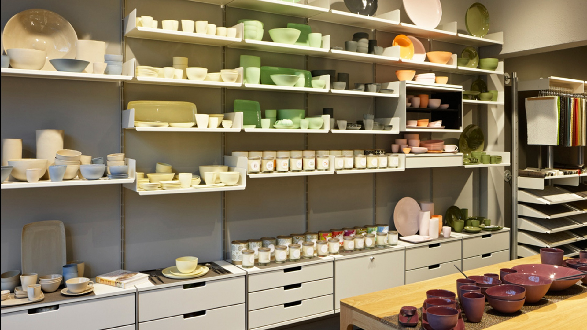 Ceramics on shelves, in drawers and behind doors. Note fabric samples on hanging rails and mats on sloping shelves. Versatile shop-fitting