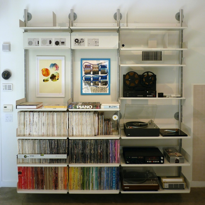 Here semi-wall mounted shelves accommodate LPs and some fine examples of Braun HiFi designed by Dieter Rams and team. Note the flat surfaces created by rotated shelves above. Use magnets to display cards and notes.