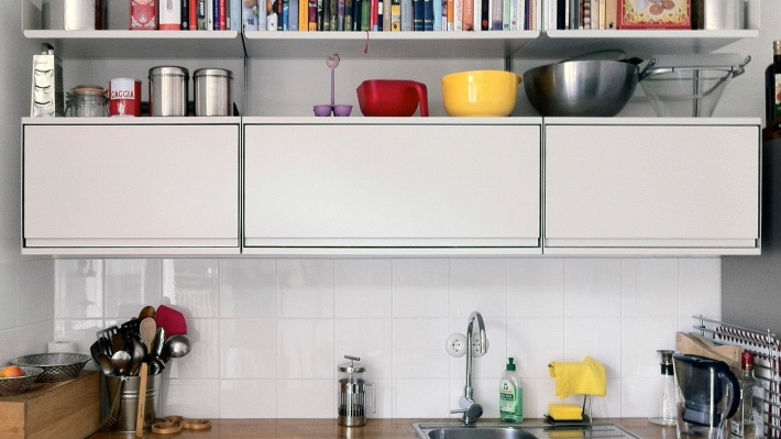 Cabinets and shelves above kitchen sink for kitchenware. Modular shelving system, strong metal, wall mounted. Vitsœ 606.