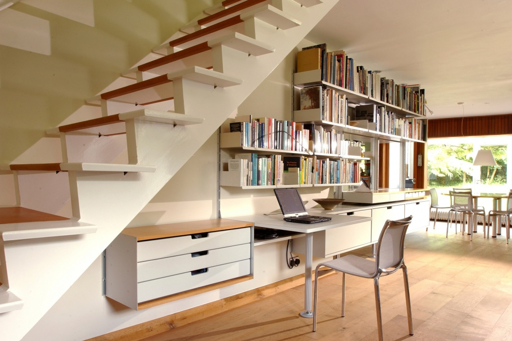 An awkward wall under the stairs can be harnessed for a table, drawers, books and extensive filing in the one-drawer cabinets