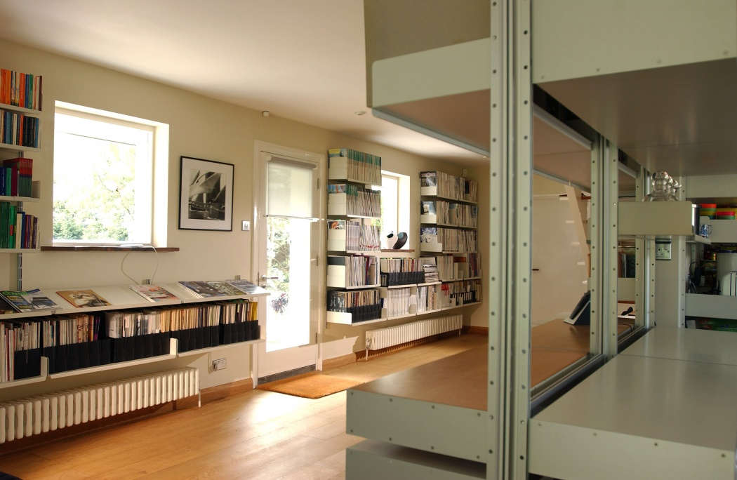 In the foreground, a system compressed between floor and ceiling; in the background, wall-mounted shelves fit around windows