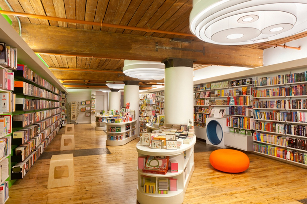 A bookshop defines its areas with black shelves to the left and off-white to the right. Lockable storage in that low cabinet