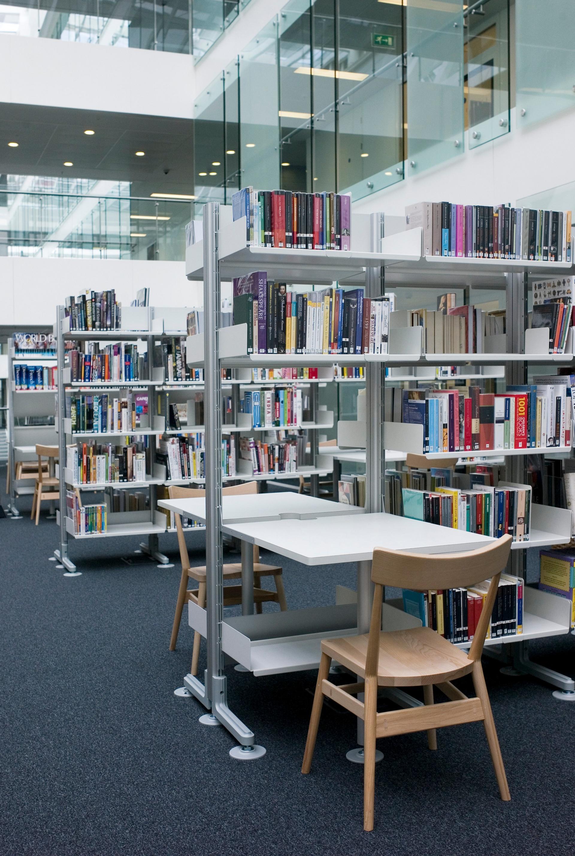 Direkt in die Regale integrierte Einhängetische schaffen Arbeitsplätze in der Bibliothek.