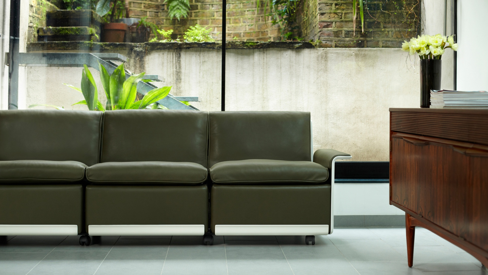 A 620 sofa sits comfortably between modern surroundings and a midcentury sideboard