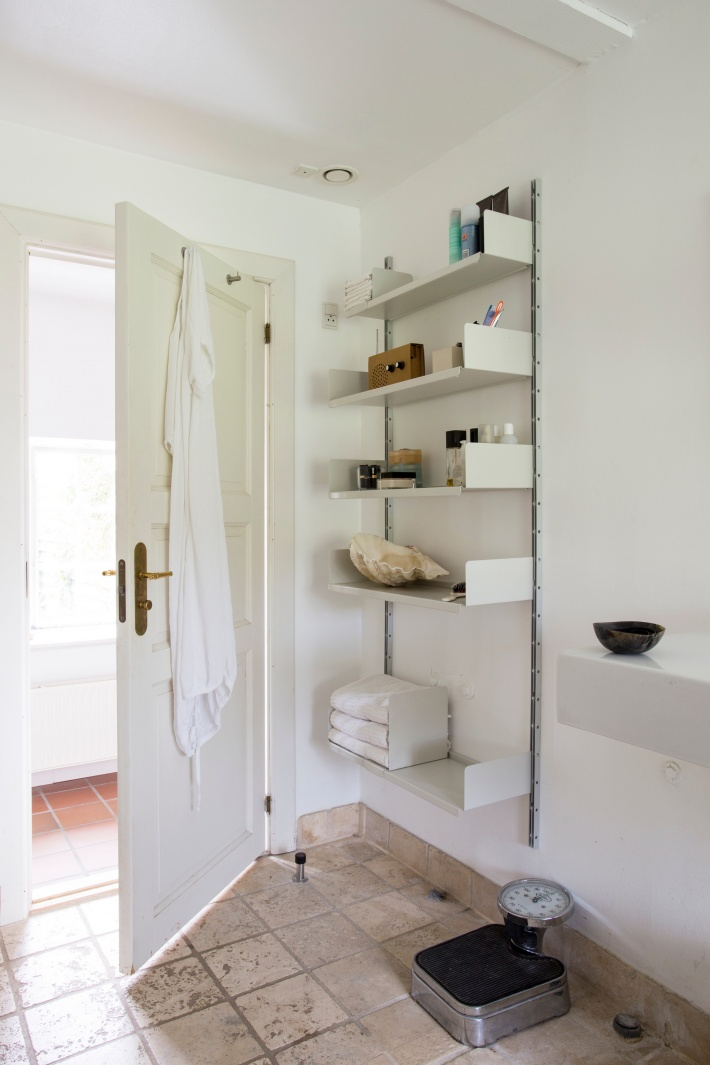 A well-placed door stop creates viable wall space behind doors. In a bathroom, open shelves allow towels to breathe.