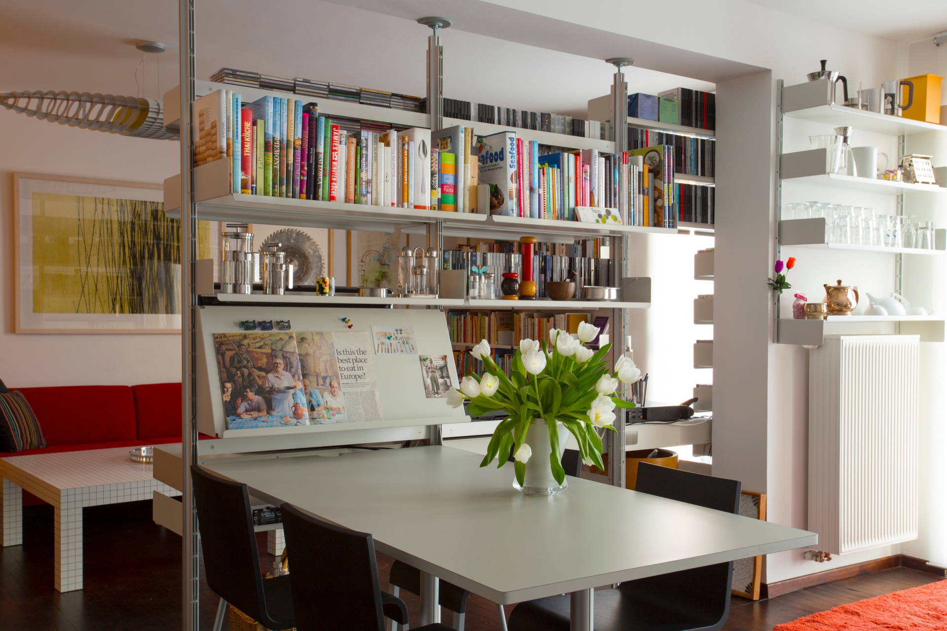 An open-plan space has been divided with a shelving system compressed between floor and ceiling which continues into wall-mounted. On this side we see an integrated table used for dining. See the other side here and note the flipped shelf above the radiator