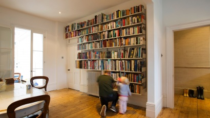 "Wall-mounted shelves find their way around a radiator and door. Shelf depths of 8½"" and 11¾"" accommodate the library"
