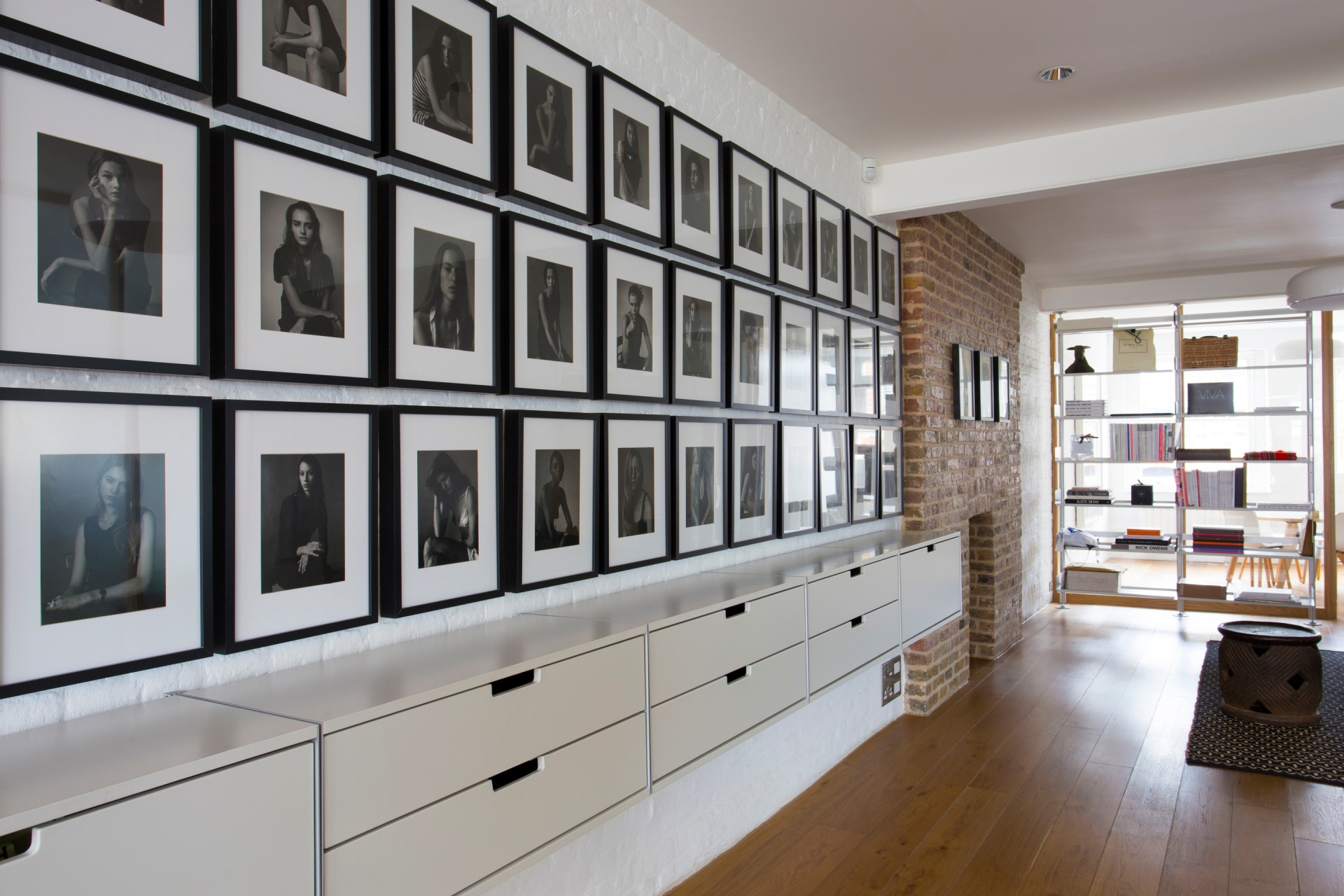 Wall-mounted cabinets on painted fair-faced bricks – below model portraits. A compressed shelving system in the background