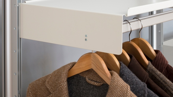 Hanging rail shelf holds clothing in a wardrobe configuration