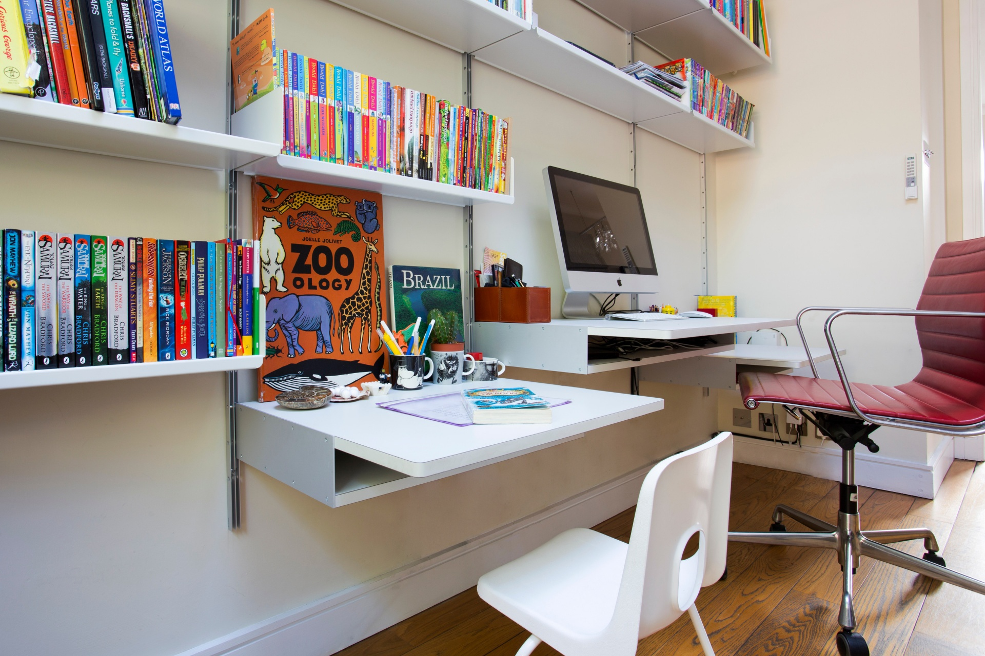 Desks at different heights for kids and grown-ups. A shelving system is for life