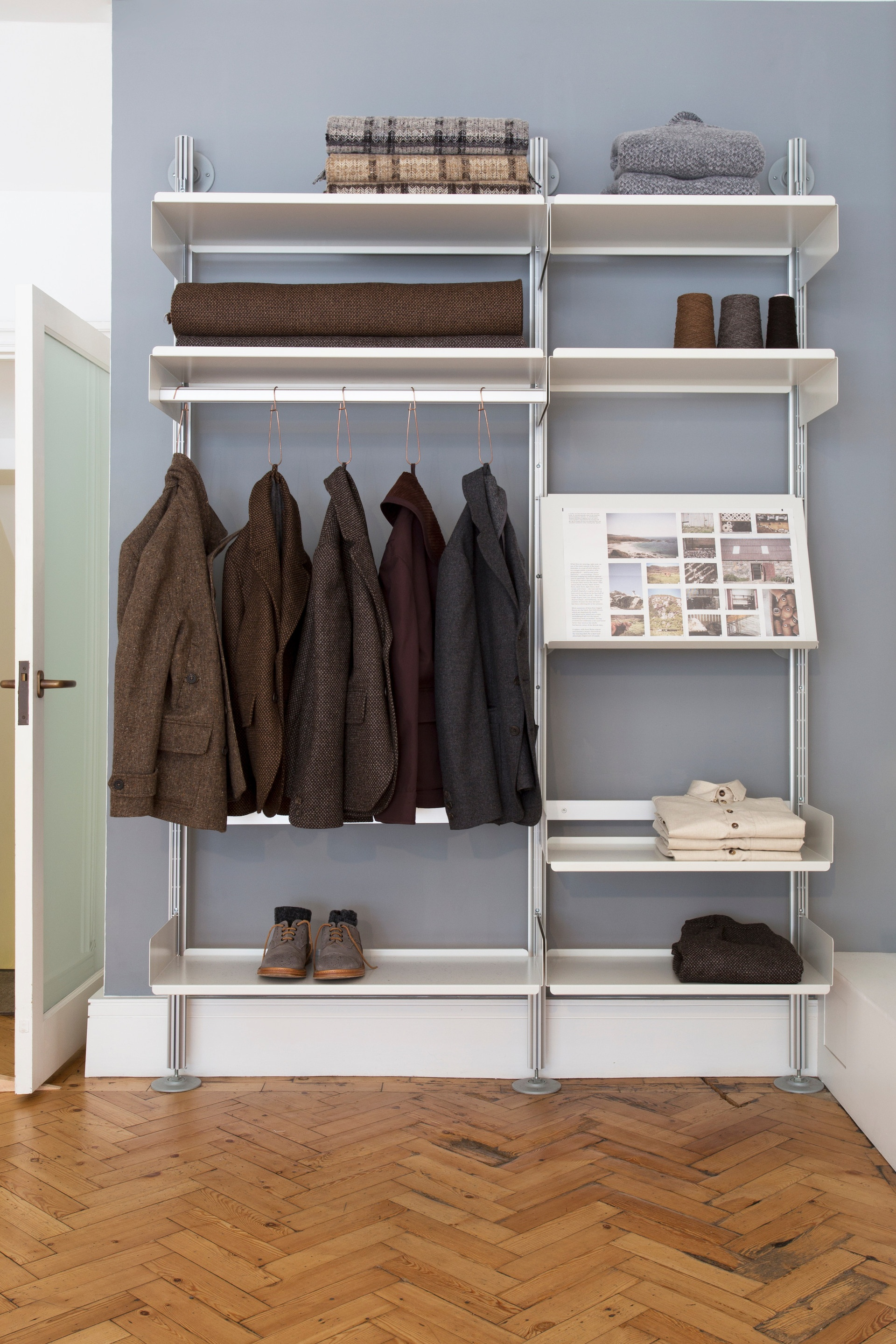 A semi-wall mounted shelving system with shelves and a hanging rail that can be rearranged at will