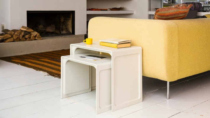 Off-white side table beside a yellow sofa
