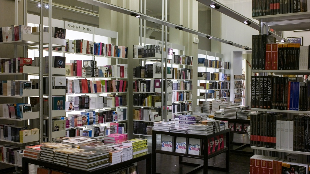 Shelves compressed between floor and ceiling store books in front of glass walls