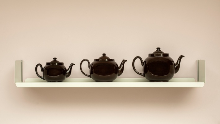 Three teapots on a Vitsœ shelf, wall-mounted.