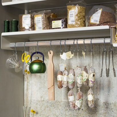 Hanging rail shelf holds kitchen utensils and foodstuffs in kitchen configuration.